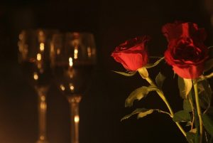 Red roses in front of wine for Valentine's Day date